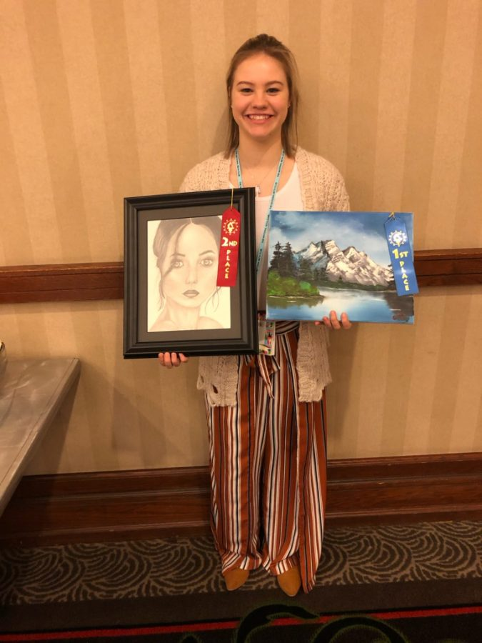 Caden Trevor with her second-place drawing and first-place painting.